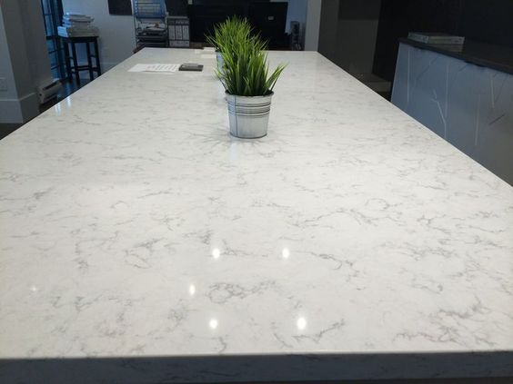 """The current dark, Formica countertops will be replaced with LG Minuet Quartz that looks a lot like marble. After pinning picture upon picture of white countertops with white cabinets, I think it's safe to assume that this is the """"feel"""" we are going for in the kitchen. The walls are a light grey (City Loft by Sherwin Williams), and we love the hue of it."""