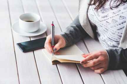 woman s hand using a pen noting on notepad